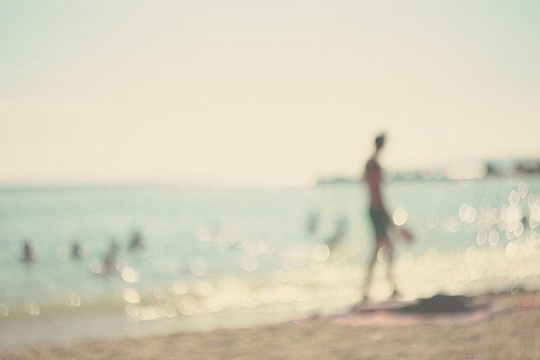 A person walks along the beach in a blurry photograph.