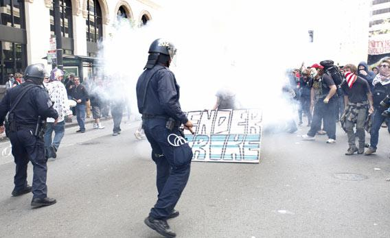Oakland police officers fire tear gas to control a group of Occupy Wall Street protesters.