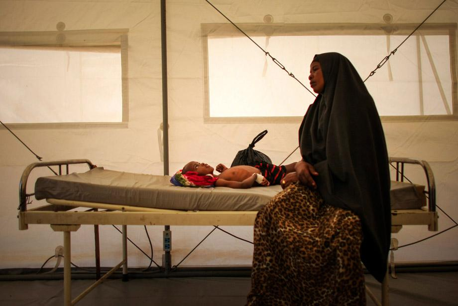 A Somali woman sits on a bed where her son has been admitted to a tented-hospital ward at a free Outpatient's Department (OPD) medical clinic at the headquarters of the Burundi Contingent serving with the African Union Mission in Somalia (AMISOM) at the former National University in the Somali capital Mogadishu, March 4, 2013.