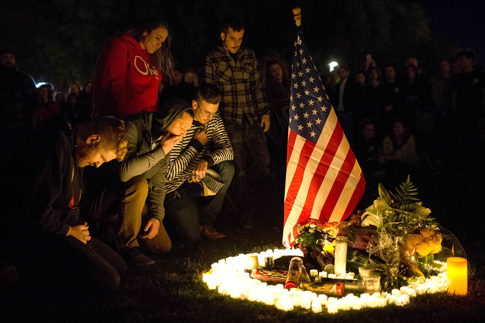 People kneel around an American flag and candles.