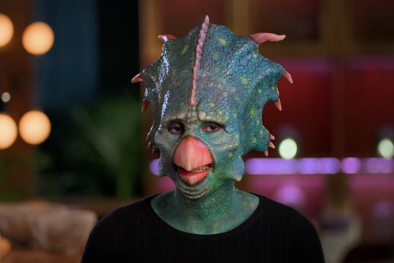 Woman dressed as a blue dinosaur.