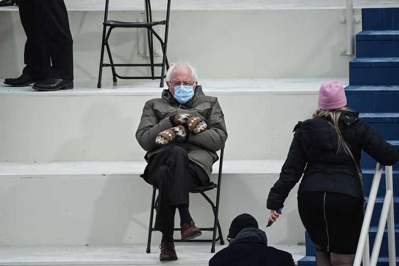 Bernie Sanders sits cross-legged in a folding chair in an olive-green coat and knit mittens.