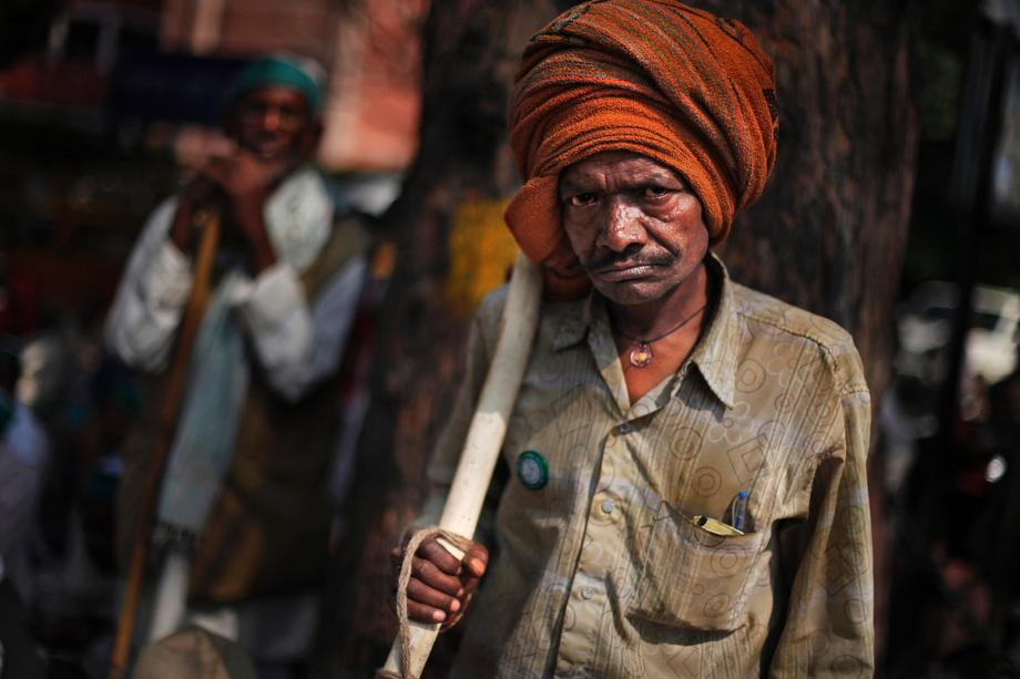 An Indian farmer, armed with a stick, reacts to the camera as he listens to a speaker, unseen, during a protest near the Indian Parliament in New Delhi, India on March 20, 2013.