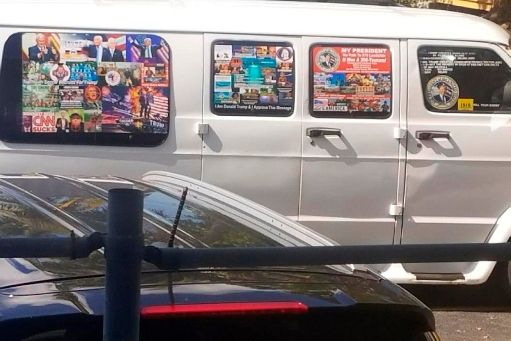 A van with windows covered with an assortment of stickers.