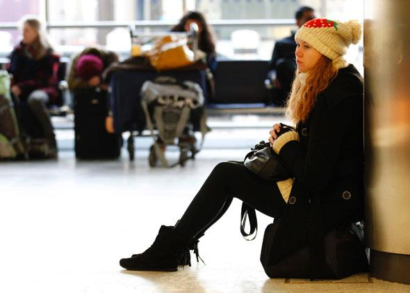 A girl sits on her bag as she waits for her flight at Edinburgh Airport, Scotland, Dec. 20, 2010.