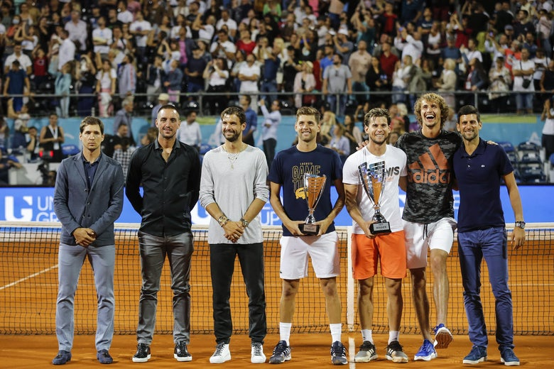 Players pose at the net for photos during Novak Djokovic's Adria Tour charity exhibition.