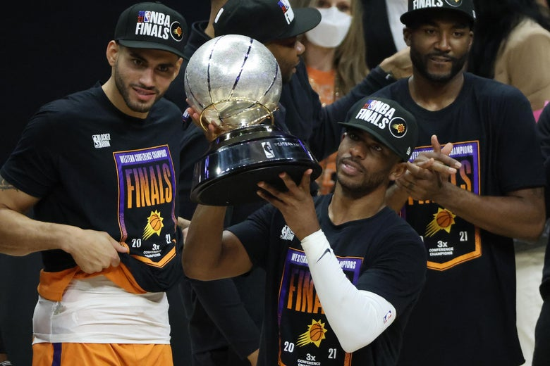 Chris Paul holds up the Western Conference championship trophy as he stands among his Suns teammates after they won Game 6