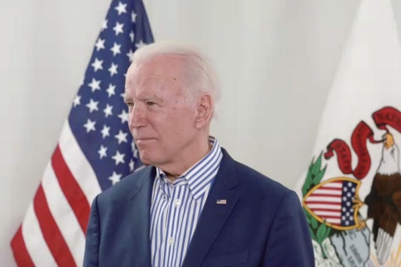 Biden stands with the American flag and Illinois flag behind him