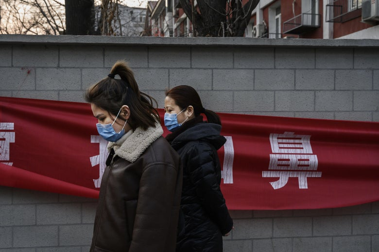 Two women wearing parkas and masks walk by a red banner.