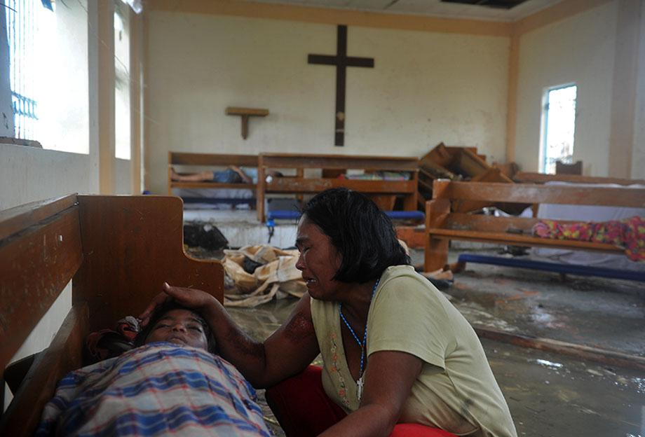 A mother weeps beside the dead body of her son at a chapel in the aftermath of Super Typhoon Haiyan in Tacloban, eastern island of Leyte on November 9, 2013.