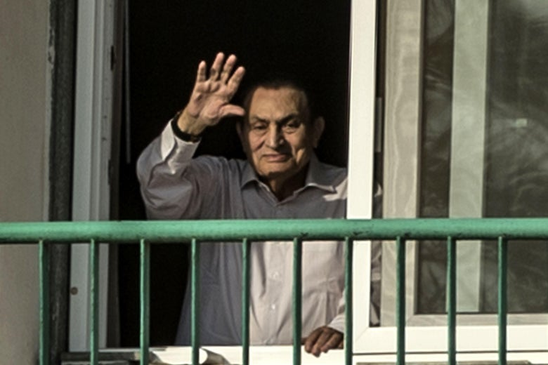 Egypt's former president Hosni Mubarak waves out a window over a railing.