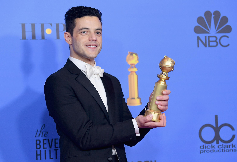Rami Malek holding a Golden Globe.