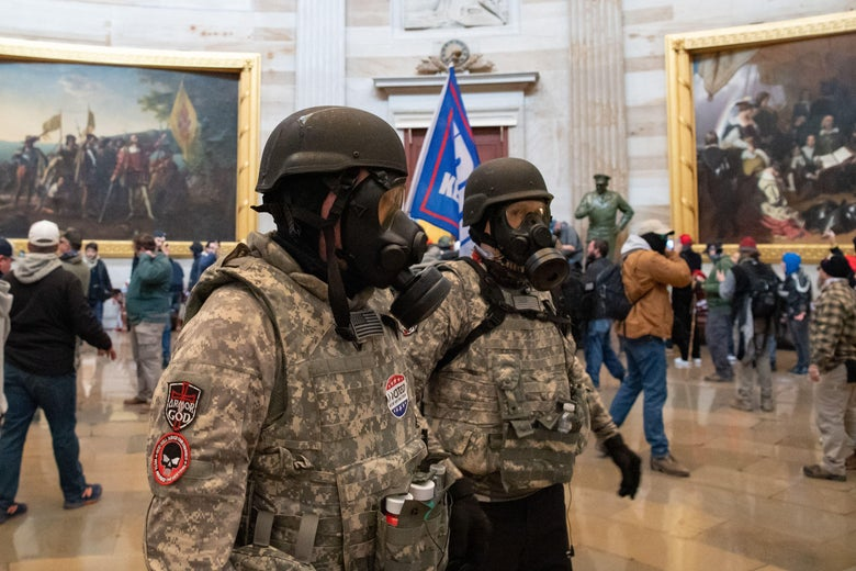Two men wearing helmets, gas masks, camouflage jackets, and bulletproof vests stand in the middle of the rotunda. Crowds of people in street clothes walk around in the background.