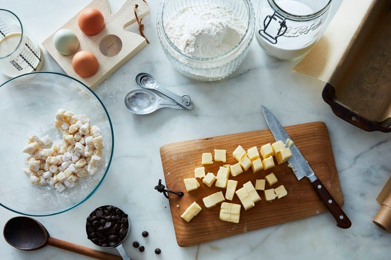 A cutting board with a knife and cubes of marzipan on it, surrounded by jars of flour and sugar, measuring cups and spoons, a bowl of balled dough, and a baking pan covered in parchment paper