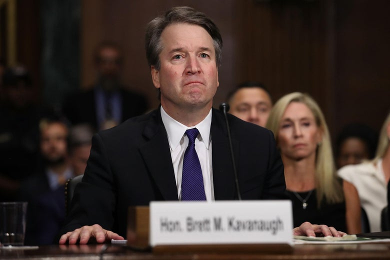 Kavanaugh, wearing a suit and seating at a table in front of an audience for the hearing, looks unhappy.