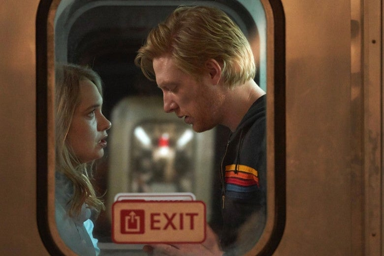 Merrit Wever and Domhnall Gleeson, sharing an intimate moment, seen through the gritty window of a train that has an Exit sign on it