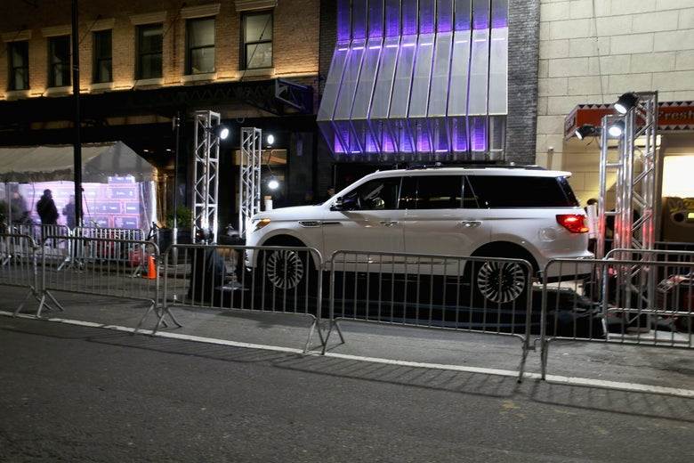 A Lincoln Navigator outside the venue, behind steel crowd control barriers.