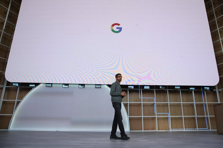 Sundar Pichai onstage in front of a huge screen displaying the Google logo.