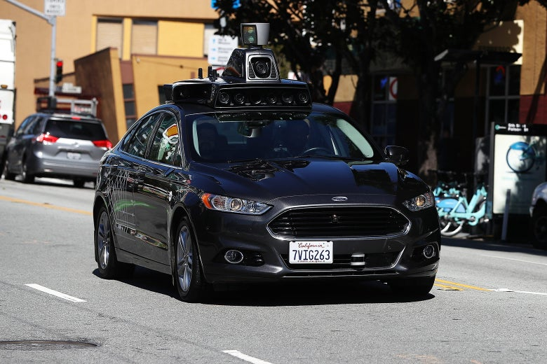An Uber self-driving car drives down the street.
