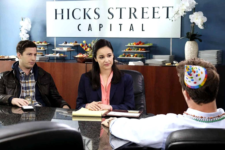 Andy Samberg and Melissa Fumero as Jake and Amy in a scene from Brooklyn Nine-Nine. Jake and Amy are seated at a conference table interrogating a finance bro wearing a party hat and beads.