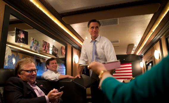 Mitt Romney rides aboard his campaign bus with Congressman Connie Mack and senior advisor Eric Fehrnstrom.
