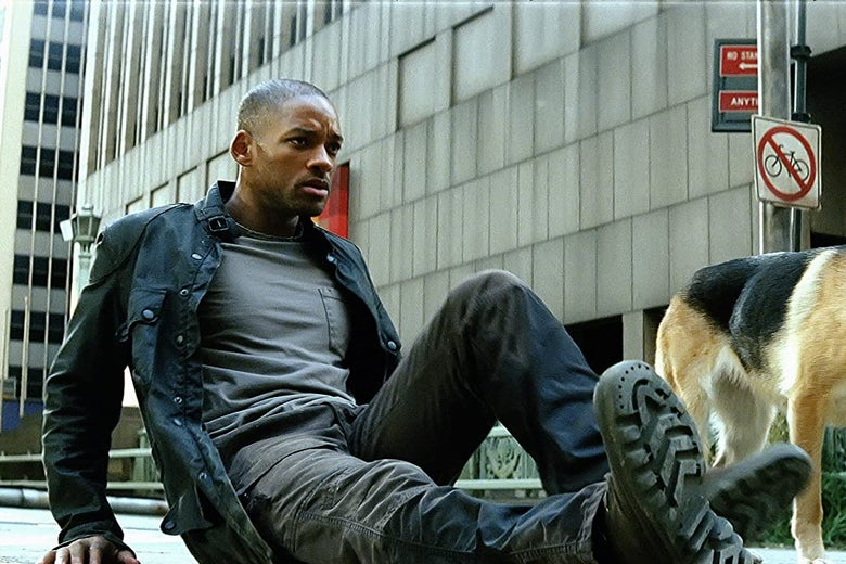 Will Smith sits on a city sidewalk, brow furrowed. A dog's rear end is in frame.