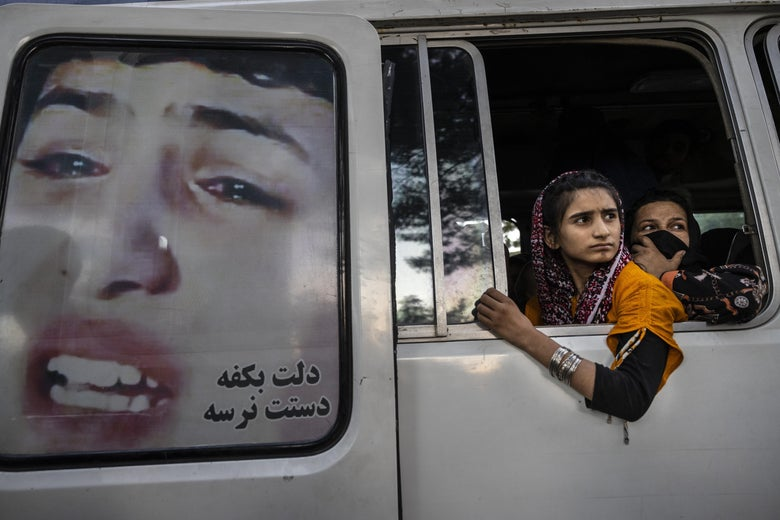 Young Afghan women look out the window of a van. There is an image of a crying woman on one of the van doors.
