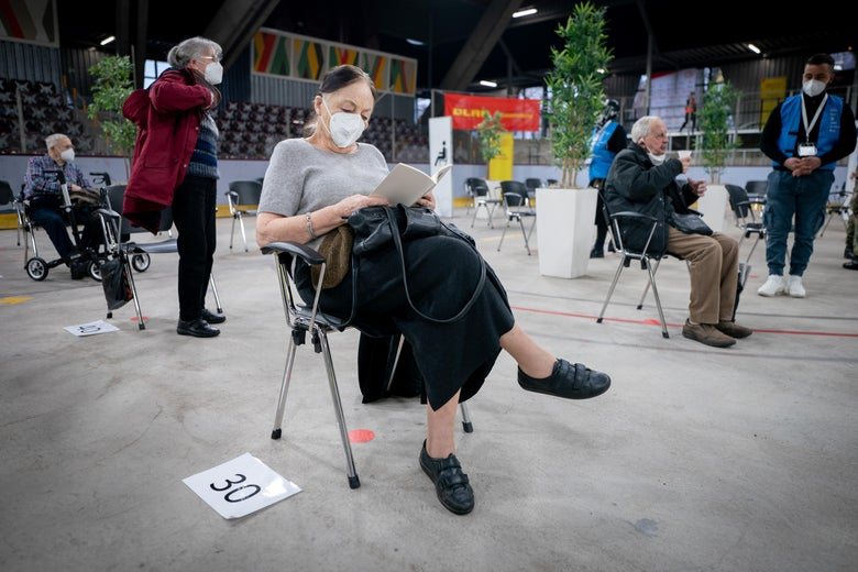 A woman waits in a chair on an ice rink