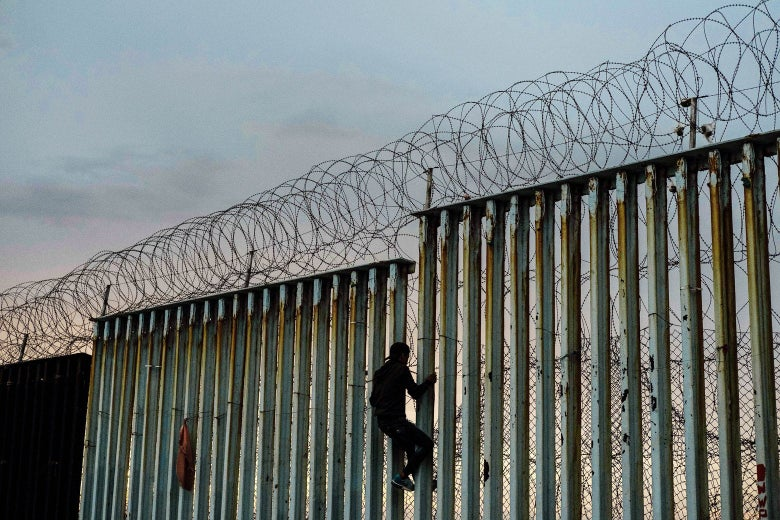 A man climbs the U.S.-Mexico border for fun in Playas de Tijuana, Mexico, on Saturday.