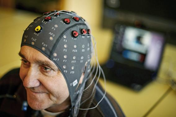 Patient Marc Andre Duc wears a cap with electrods next to a computer during a presentation of brain-machine interface by the Swiss Federal Institutes of Technology of Lausanne  on January 23, 2013 in Sion.