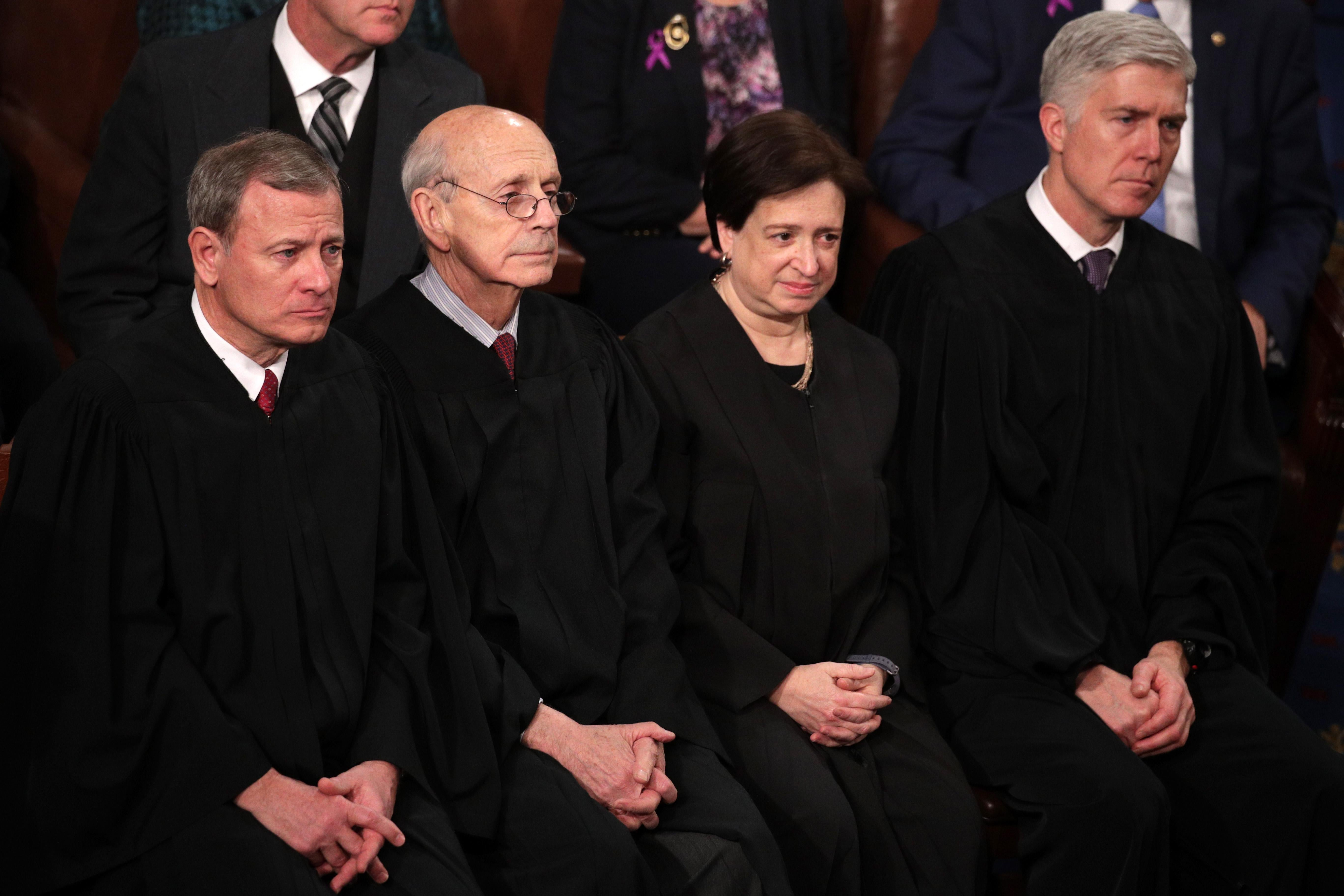 The four justices seated, wearing black robes.