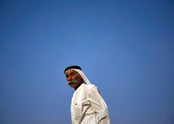 Abu Aziz stands outside his tent in the village of al-Arakib, one of the dozens of ramshackle Bedouin Arab communities in the Negev desert which are not recognised by the Israeli state, in southern Israel August 18, 2013.