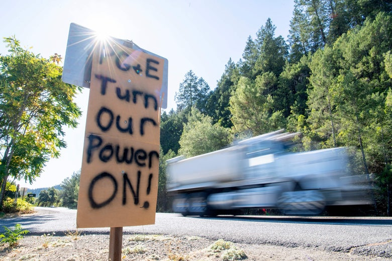 "A sign that says ""PG&E Turn Our Power On!"" by the side of a highway."