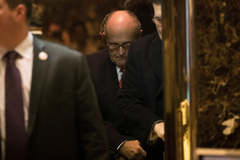 Rudy Giuliani looks toward the floor, as if ashamed, from inside an elevator.