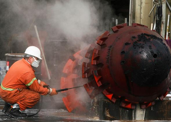 A worker uses a pressure hose to clean part of the Trans-Alaska Pipeline Marine Terminal in Valdez, Alaska, where oil flows from oil fields in Prudhoe Bay