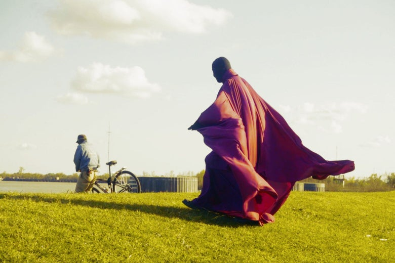 In this still from The Fathers Project, a person in a billowing full-body outfit walks in a park.