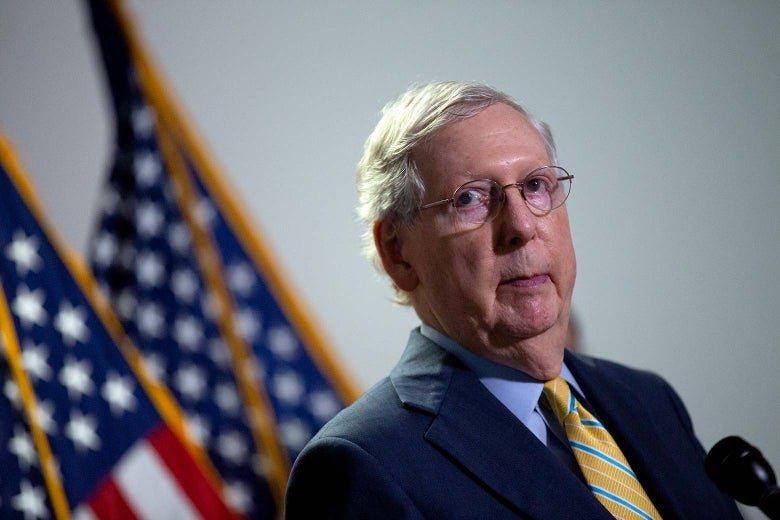 McConnell stands at a mic with two American flags in the background