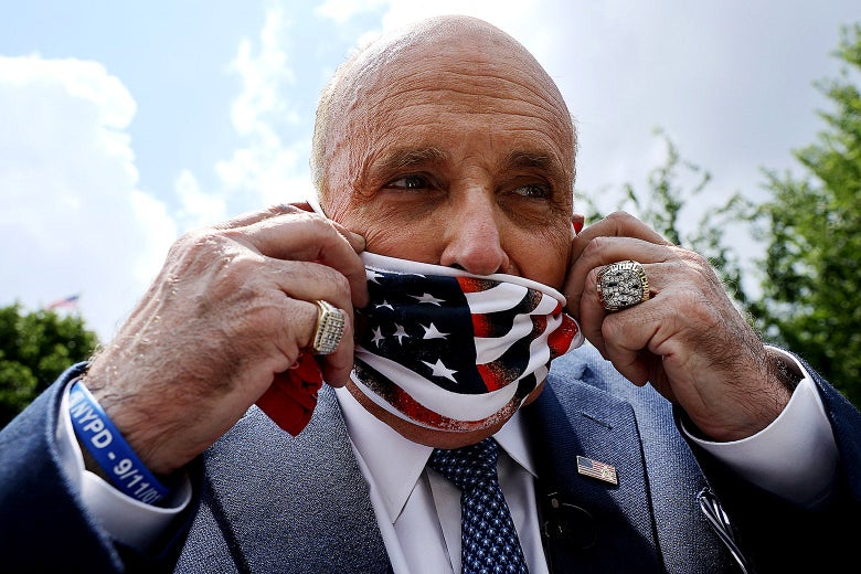 Close-up of Giuliani putting on an American flag face mask