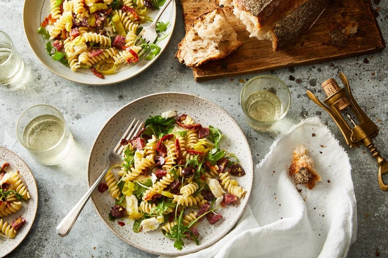 Pasta with greens, sun-dried tomatoes, olives and a fork on plates near bread.