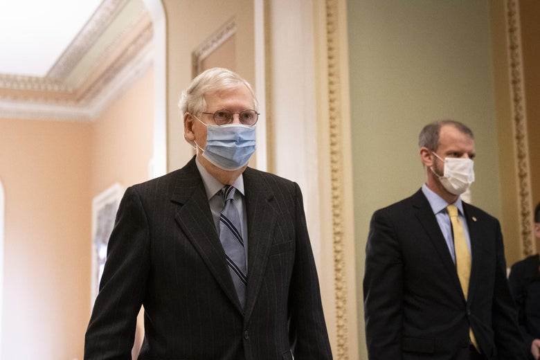 McConnell, wearing a mask, walks in a hallway