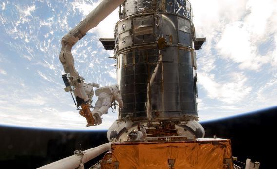 Astronauts work to refurbish and upgrade the Hubble Space Telescope.