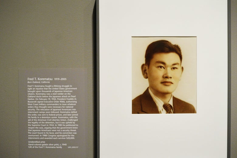 A framed sepia-toned portrait of Fred Korematsu on a gray wall with explanatory text next to it.