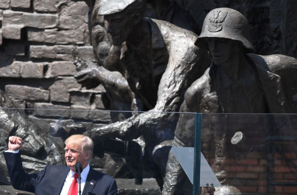 Trump raises his fist in front of a large statue of a soldier.