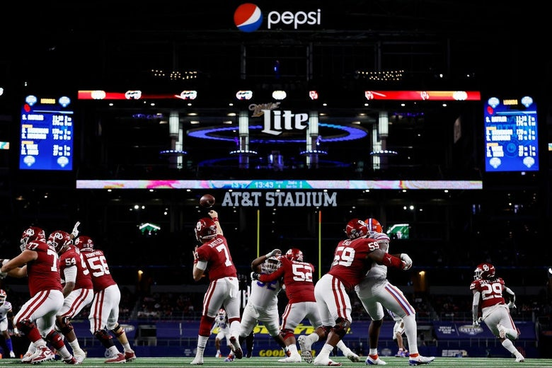Rattler throwing a pass amid a number of offensive and defensive linemen, with logos for Goodyear, AT&T, Miller Lite, and Pepsi gleaming above against the dark backdrop of the stadium.