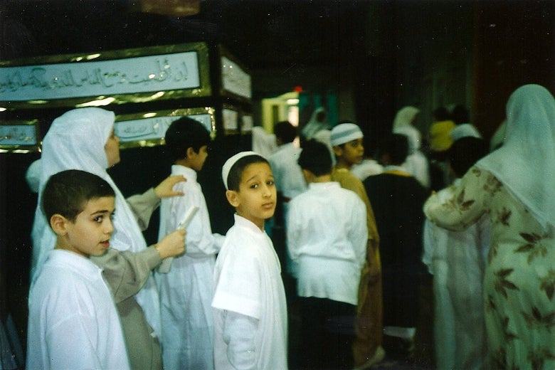 Young boys dressed in white file into a gym for a practice hajj.