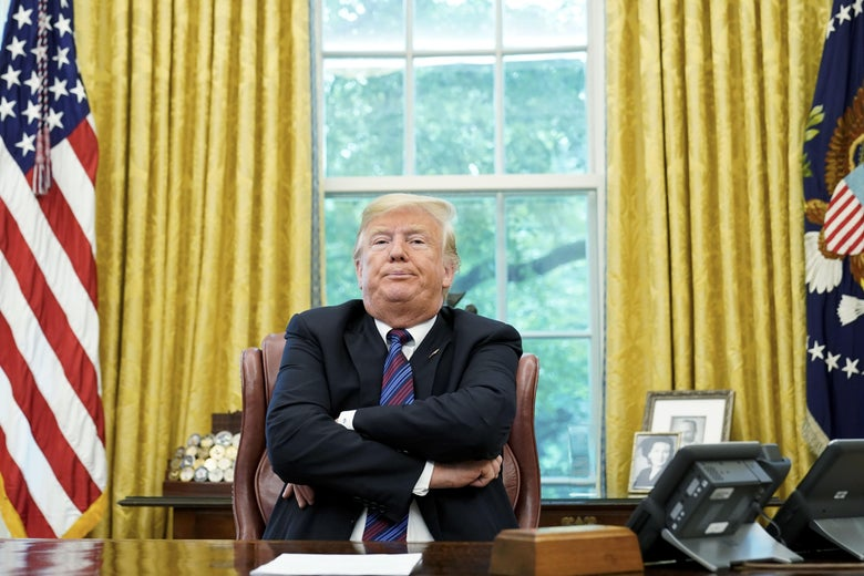 President Donald Trump sits at his desk in the Oval Office with his arms crossed and chin jutting out.