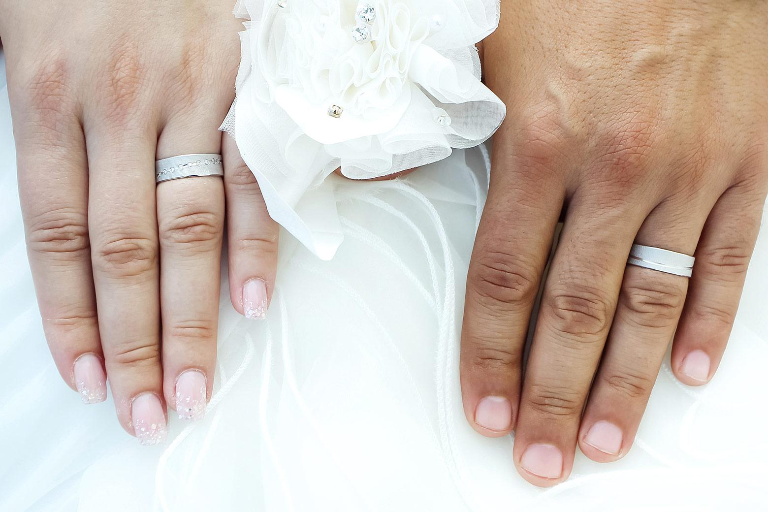 The wedding bands on a married couple flank a bow.