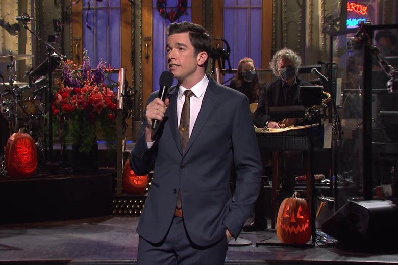 John Mulaney standing on the SNL main stage, in a grey suit, holding a microphone and telling a joke.