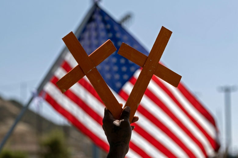 A hand holds two crosses in front of a U.S. flag.