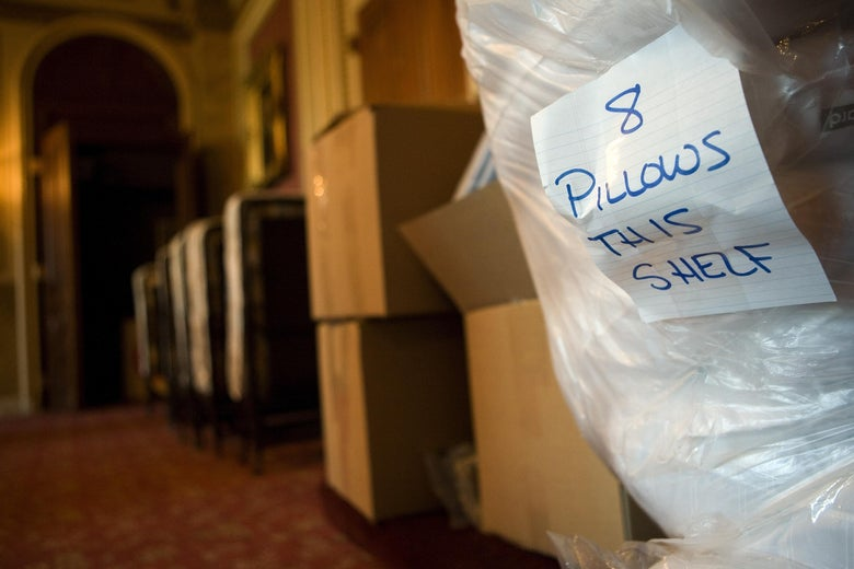 """A piece of lined paper that says """"8 pillows this shelf"""" taped to a large plastic bag of bedding next to some cardboard boxes in a hallway"""